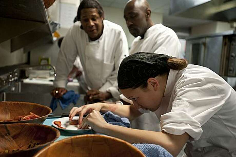 Seaera Magsino (right) meticulously arranges the items of her salad as Louis Miller (center) and Hans Price look on as the CHEFS program at Episcopal Community Services in San Francisco, Calif, holds a competition between the current class, number 38, and the previous class, number 37 and prepare their dishes for judging on Thursday, August 12, 2010. Photo: Chad Ziemendorf, The Chronicle