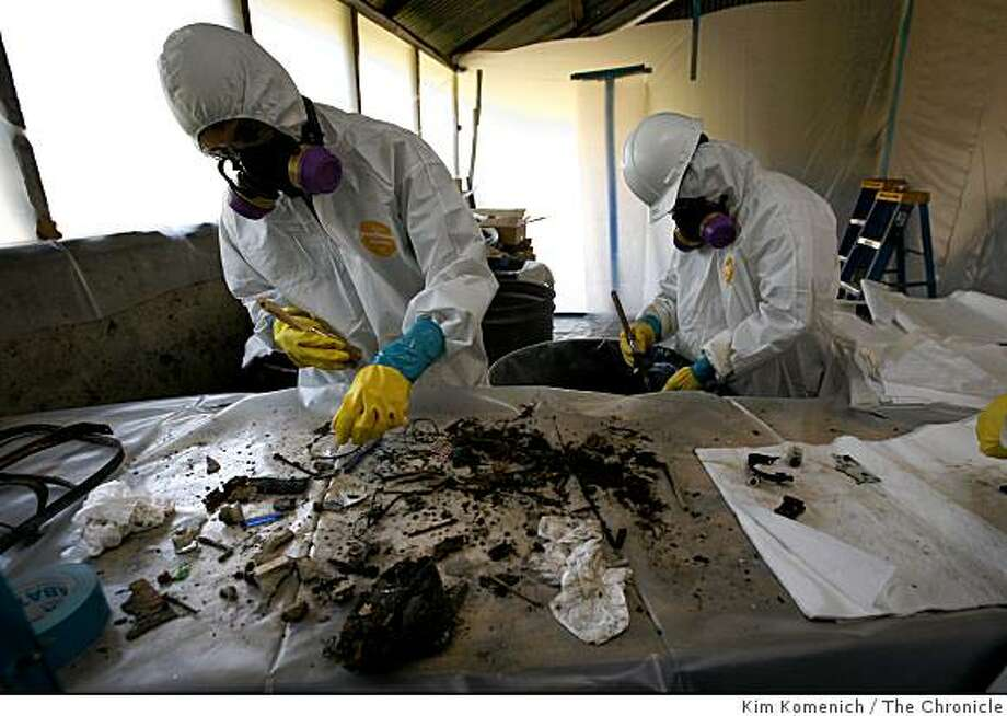 Workers dressed in hazmat protective clothing remove asbestos and other dangerous substances from artifacts found on the site of the former Burdell Mansion at Olompali State Historical Park north of Novato, Calif., on Tuesday, Jan. 13, 2009. Before it burned on Feb. 2, 1969, the mansion was a hippie scene which housed, among others, the members of the Grateful Dead and Janis Joplin. Photo: Kim Komenich, The Chronicle