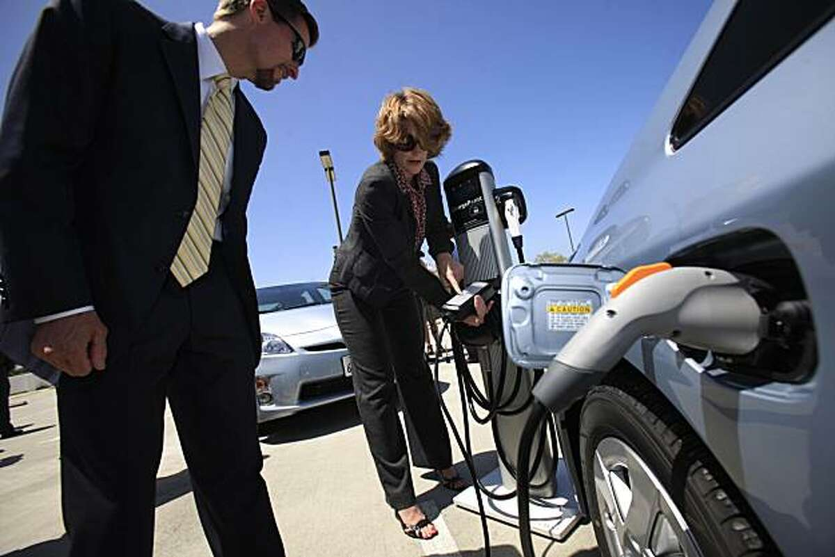 Tom Werner (left), CEO of SunPower, watches as Jana Hartline (right), Manager, Environmental Communications with Toyota, demonstrates the use of a 22 foot power charging cable with a demo of demo of Coulomb Technologies' ChargePoint Networked Charging Station and a Toyota Prius Plug-in Hybrid Vehicle in San Jose, Calif. on Tuesday June 15, 2010. The cable comes with the Toyota Prius Plug-in Hybrid Vehicle. Silicon Valley Leadership Group received three Toyota Prius Plug-in Hybrid Vehicles as Toyota Motor Sales, USA, Inc launches its U.S. plug-in demonstration program.