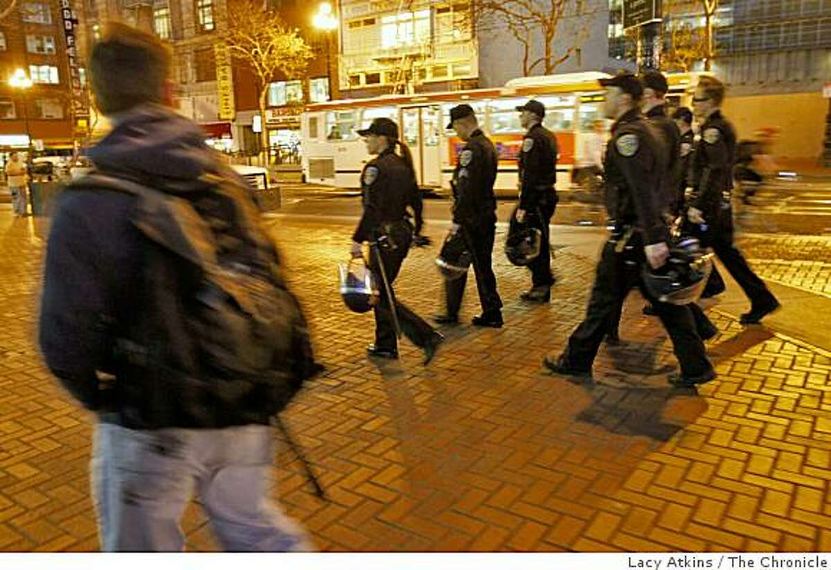 Police officer walk down Market street in preparation of the protesters marching to Powell Street from the BART's Civic Center , where they rallied over the killing of Oscar Grant , Monday Jan. 12, 2009, in San Francisco, Calif.