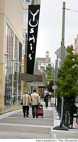 Pedestrians walk past the new Yoshi's Club on Fillmore Street in San Francsico, Calif., on Tuesday, July 15, 2008. San Francisco's Redevelopment Agency is set to leave the Western Addition in January, ending a 40-year urban renewal project that was touted as a move to wipe out blight. In the process the project dispersed San Francisco's largest thriving black community. Photo: Kim Komenich, The Chronicle
