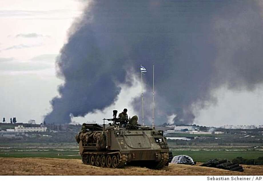 Israeli soldiers sit on top of an armored vehicle as smoke rises from Gaza near Israel's border with the Gaza Strip, Sunday, Jan. 11, 2009. Israeli ground troops made their deepest advance into the Gaza Strip's most heavily populated area on Sunday, encountering fierce resistance from Islamic Hamas fighters as residents of the war-ravaged territory braced for a sharp escalation in fighting in defiance of global calls for a cease-fire. (AP Photo/Sebastian Scheiner) Photo: Sebastian Scheiner, AP