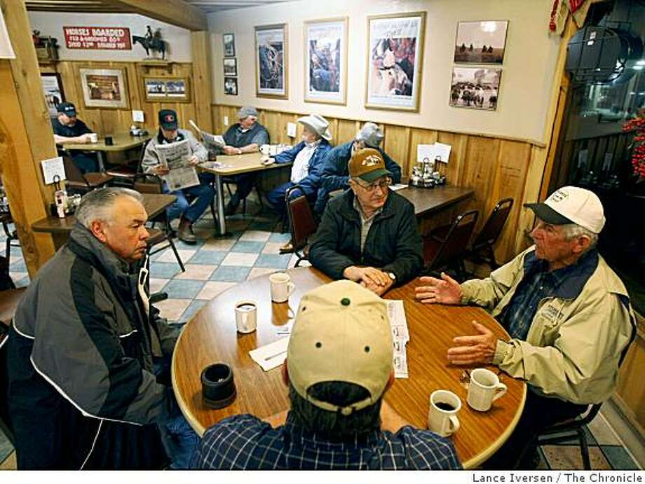 An informal meeting of dairymen takes place each morning before dawn at the Farmers Den Cafe in Turlock. Ray Souza left chats with fellow dairyman as they wait to hear what the current price for milk. Due to the recession and lack of international demand for American dairy products the price has fallen to almost half what it was six months ago. Saturday Jan 10, 2009 Photo: Lance Iversen, The Chronicle