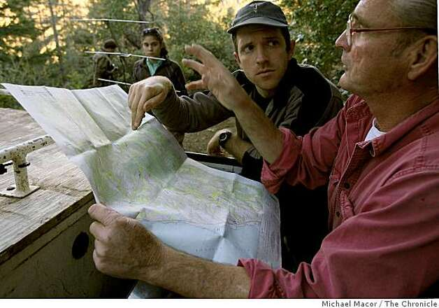 Paul Houghtaling, (center) and Houndsman, Cliff Wylie (right) pour over a map as they discuss the best way into the forest to begin tracking a mountain lion they are currently studying which is equipped with a radio transmitting collar used in researching and locating the cat, near Santa Cruz, Calif on Tuesday Dec. 3, 2008. Photo: Michael Macor, The Chronicle