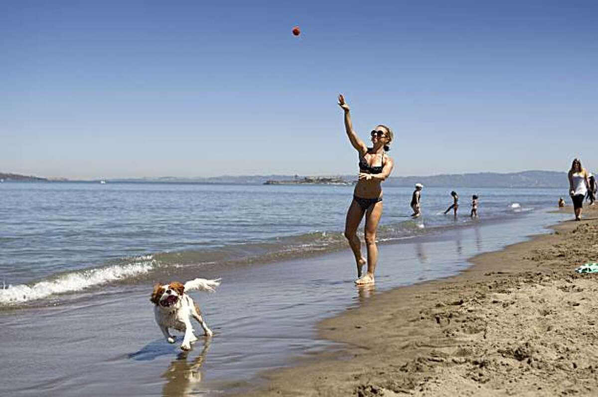 Nicole Wenzel throws a ball for her dog Lola while enjoying the hot weather at Crissy Field in San Francisco on Tuesday.