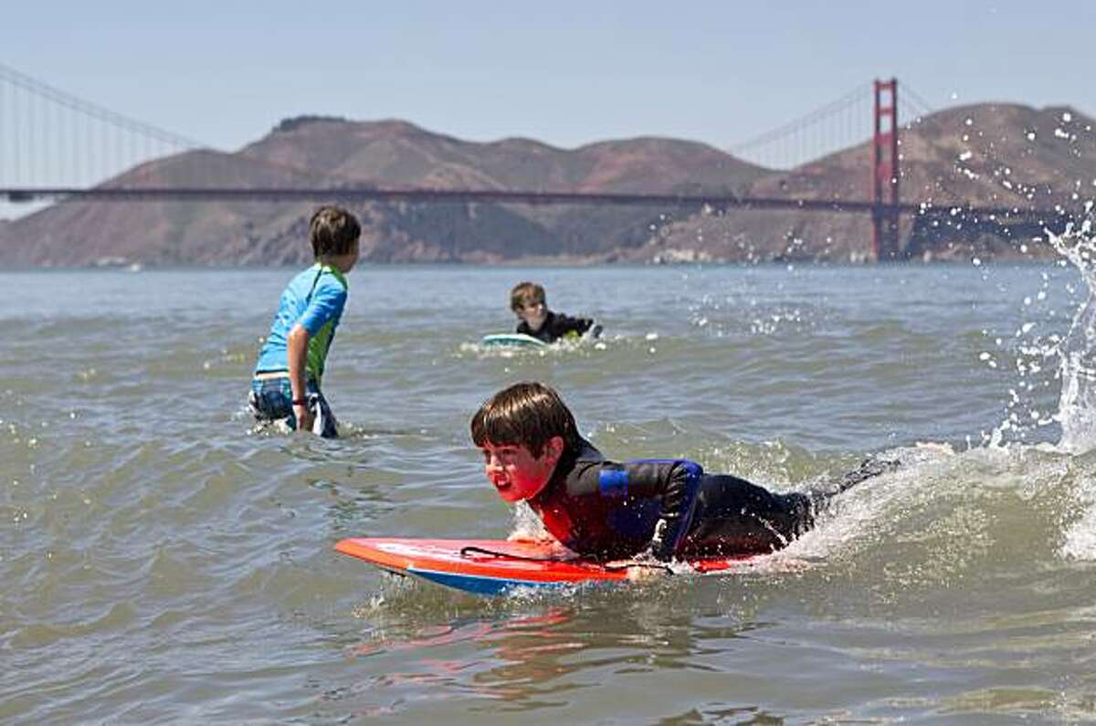 Radley Peschel, 12, catches a wave on his board while playing in the water at Crissy Field in San Francisco on Tuesday.