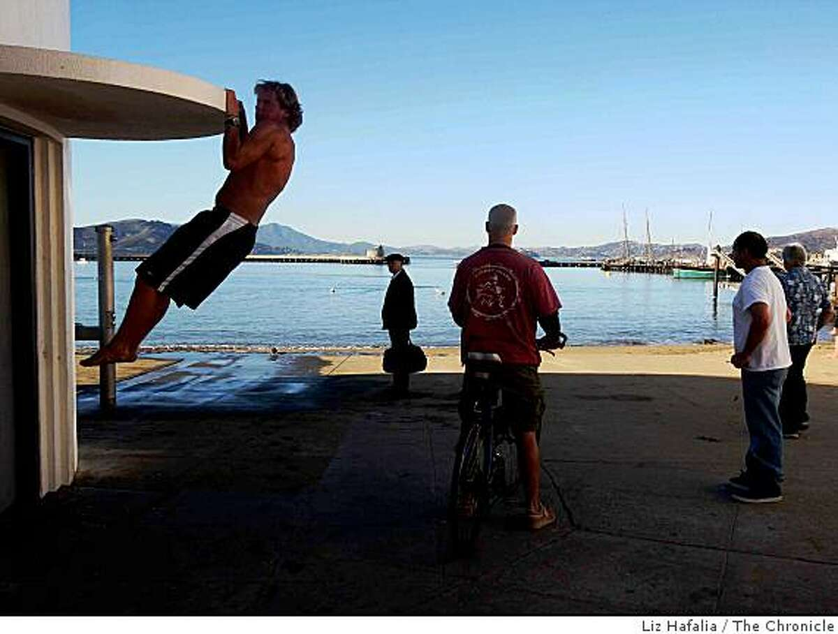 Robert Hardy (left) from San Francisco doing a few pull ups at Aquatic Park in San Francisco, Calif., on Monday, January 12, 2009.