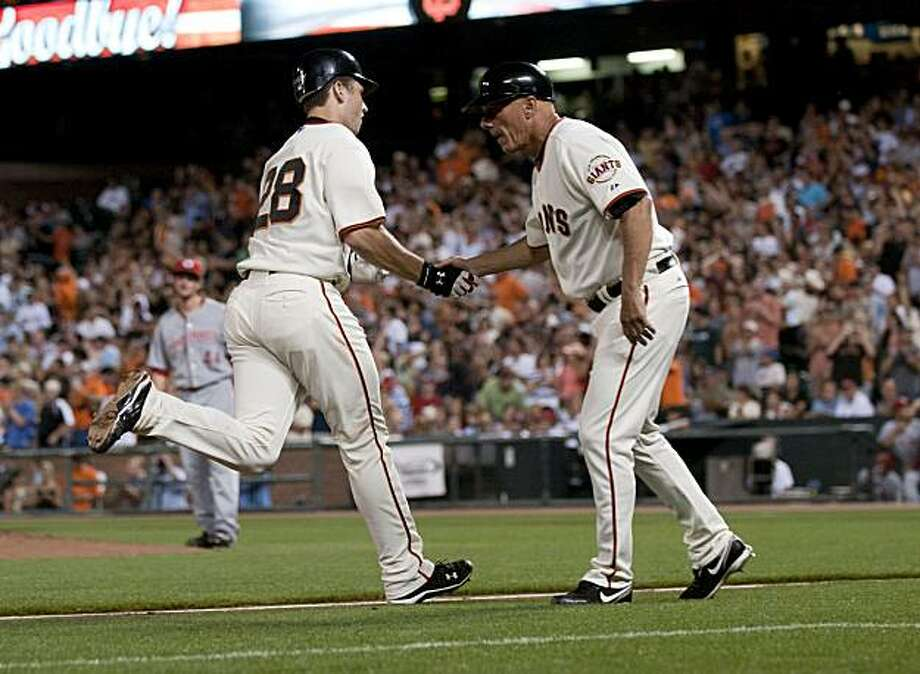 Buster Posey is congratulated by third base coach Tim Flannery after his 5th inning home run as The San Francisco Giants take on the Cincinnati Reds at AT&T Park in San Francisco, Calif., on Tuesday, August 24, 2010. Photo: Chad Ziemendorf, The Chronicle