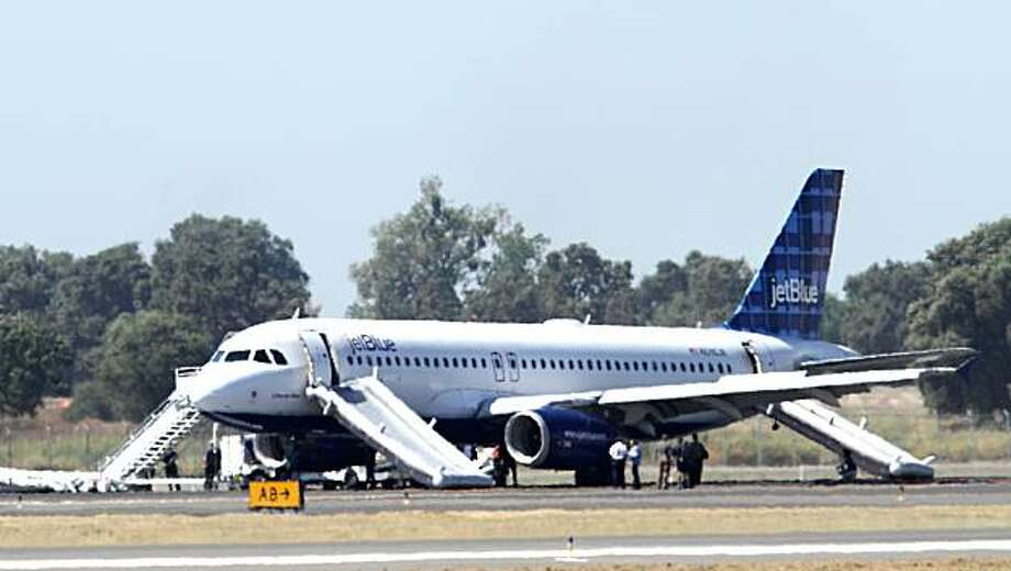 A JetBlue airplane that blew two tires while making a hard landing, forcing the evacuation of 92 passengers and crew down inflatable slides, rests on the tarmac at Sacramento International Airport in Sacramento, Calif., Thursday, Aug. 26, 2010. Photo: Rich Pedroncelli, AP