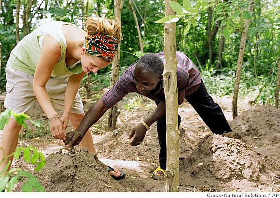 In this recent undated photo released by Cross-Cultural Solutions, a volunteer with the Cross-Cultural Solutions, left, assists a local farmer in gardening in Ghana. The volunteer was on a trip organized by Cross-Cultural solutions, a New Rochelle, N.Y.-based group, for a trip to Ghana. Photo: Cross-Cultural Solutions, AP