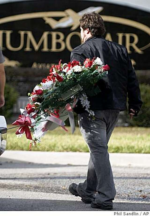 A florist delivery worker carries a wreath of flowers at the entrance to Jumbolair Aviation Estates, where actor John Travolta and his family have a home Wednesday, Jan. 7, 2009  near Ocala, Fla. Friends and relatives are expected for a ceremony Thursday to be held for the death of the Travolta's sixteen year old son Jett, who died while in the Bahamas. (AP Photo/Phil Sandlin) Photo: Phil Sandlin, AP