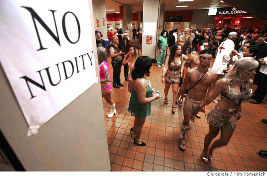 EXOTIC28_069_KK.JPG  scantily clothed folks walk past the no nudity sign in the entryway to the 2007 Exotic Erotic Ball at the Cow Palace.  Photo by Kim Komenich/The Chronicle  **  Ran on: 10-28-2007 Photo: Kim Komenich