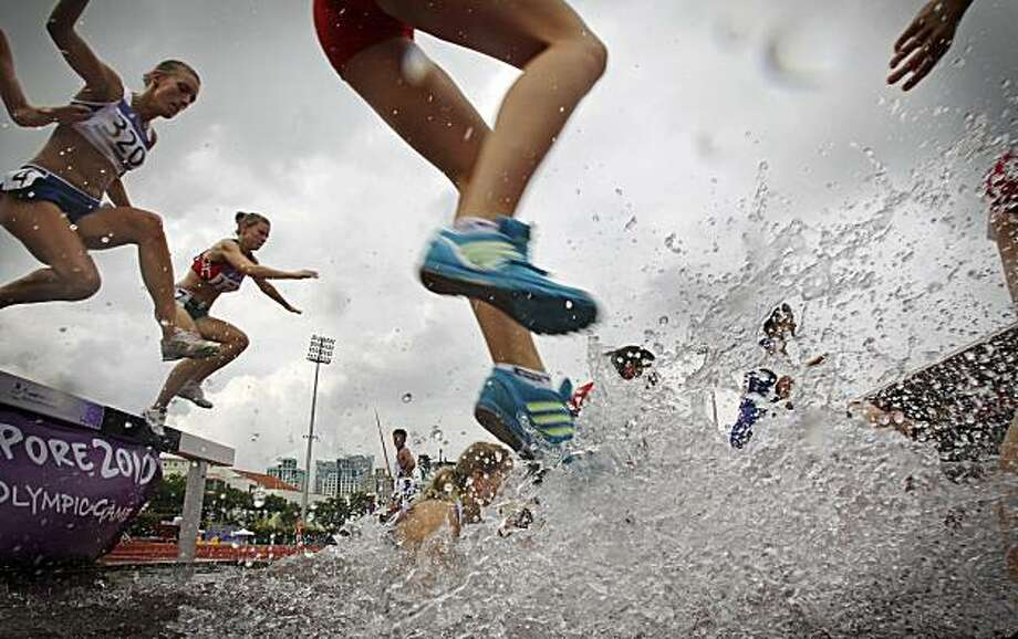 Nina Harbold of France, left, and Anastasiya Puzakova of Bulgaria, second from left, compete in the women's 2000-meter steeplechase event at the Youth Olympics on Wednesday Aug. 18, 2010, in Singapore. Photo: Wong Maye-E, AP