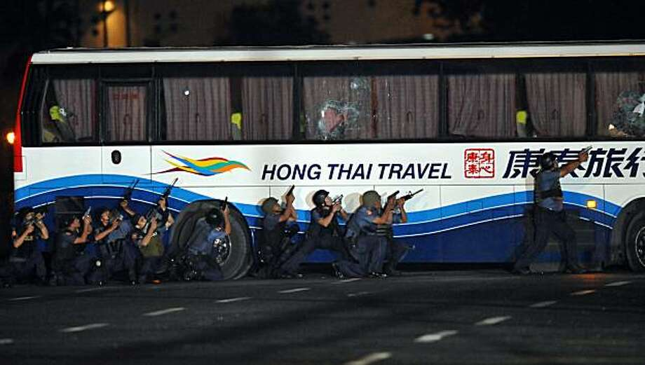 Philippine policemen move to take control of a bus full of Hong Kong tourists hijacked by an ex-policeman on August 23, 2010 in Manila.  The security forces stormed the bus, putting to end a dramatic hostage crisis that unfolded live on global television,leaving at least seven people and the gunman dead. Photo: Ted Aljibe, AFP/Getty Images