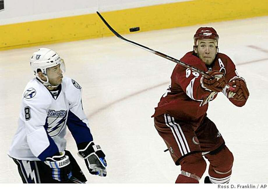 Phoenix Coyotes defenseman Derek Morris, right, tries to hit the puck as Tampa Bay Lightning right wing Mark Recchi (8) tries to avoid the stick in the second period of an NHL hockey game Thursday, Jan. 8, 2009, in Glendale, Ariz. The Coyotes defeated the Lightning 3-2. (AP Photo/Ross D. Franklin) Photo: Ross D. Franklin, AP