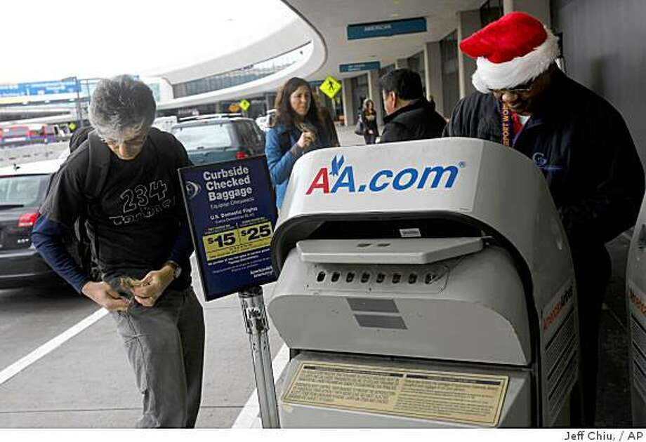 Arman Garakani, left, gets money out to pay baggage fees to a skycap at the American Airlines bag drop at San Francisco International Airport in San Francisco, Tuesday, Dec. 23, 2008. Frustration has been a common reaction since airlines in the spring began instituting first and second checked bag fees on domestic flights to help offset soaring fuel prices. Oil has plunged dramatically in the months since, but the fees have remained. Photo: Jeff Chiu,, AP