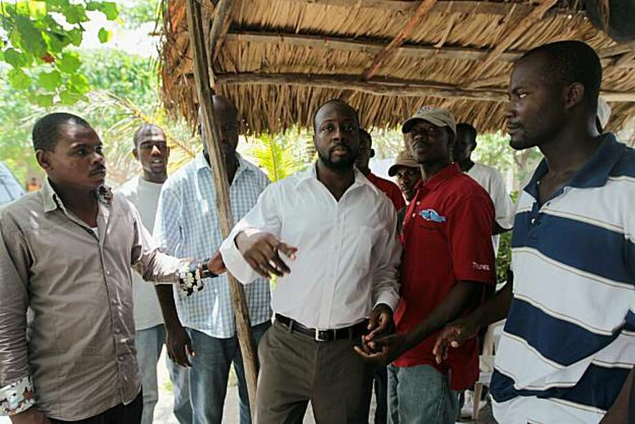 PORT-AU-PRINCE, HAITI - AUGUST 19:  Singer Wyclef Jean (C) greets his neighbors before heading off for a meeting with Haitian President Rene Preval on August 19, 2010 in Port-au-Prince, Haiti. Haiti's electoral authorities are scheduled to release the list of the presidential candidates that can run in the November 28, 2010 election on August 20. There is 1.5 million people still living in tent camps and less than four percent of the rubble from collapsed buildings has been cleared since the earthquake, that killed some 200,000 people. Photo: Joe Raedle, Getty Images