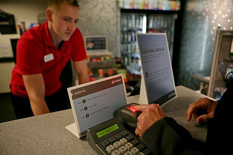 24-Hour Fitness employee Aaron Causey signs up a gym member for the new cardless check-in system, which uses fingerprints. Photo: John Sebastian Russo, The Chronicle