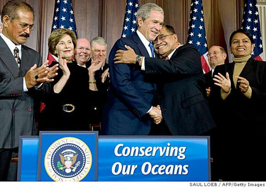 "US President George W. Bush embraces Governor Benigno Fitial (2nd R) of Northern Mariana Islands after signing a proclamation announcing the creation of the world's largest marine protection area during a ceremony at the Eisenhower Executive Office Building near the White House in Washington, DC, on January 6, 2009.  The three areas, designated as ""marine national monuments,"" include the Mariana Trench and northern Mariana Islands, the Rose Atoll located in American Samoa and a chain of remote islands in the Central Pacific. AFP PHOTO / Saul LOEB (Photo credit should read SAUL LOEB/AFP/Getty Images) Photo: SAUL LOEB, AFP/Getty Images"