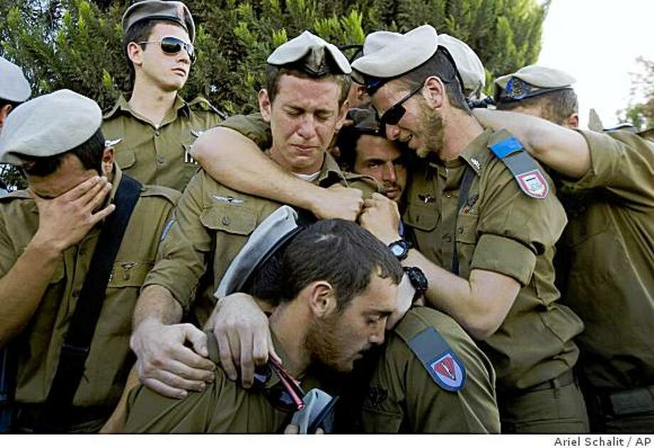 Israeli soldiers mourn during the funeral of their comrade Staff Sgt. Alex Mashavisky in the military cemetery of the southern Israeli town of Beersheba, Wednesday, Jan. 7, 2009. Mashavisky was killed Jan. 6, during the Israeli army operations in the Gaza Strip. Six Israeli soldiers had been killed and about 300 of the more than 670 Palestinians killed so far in the operation are civilians, according to Palestinian and U.N. figures. (AP Photo/Ariel Schalit) Photo: Ariel Schalit, AP