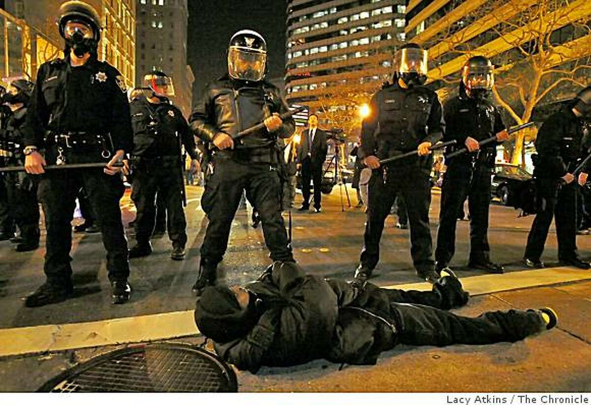 Jefeabo Wellington lays down in front of the police along Broadway during a protest in downtown Oakland, Wed. Jan 7, 2009, in Oakland, Calif.