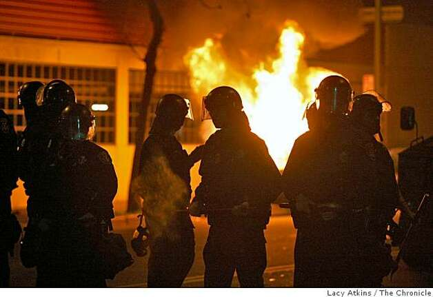 Oakland Police Officers are silhouetted as a car burns in the background. Police moved protesters down 14th street where cars were vandalized during the riot through the streets in downtown Oakland, Wed. Jan 7, 2009, in Oakland, Calif. Photo: Lacy Atkins, The Chronicle