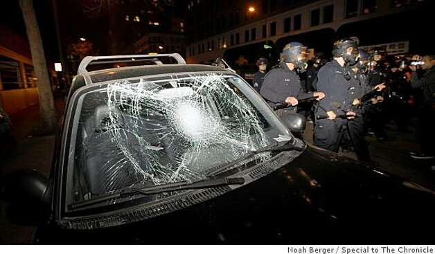 Police in riot gear march past a broken car window during a protest in downtown Oakland, Calif. on Wednesday, Jan. 7, 2009. Photo: Noah Berger, Special To The Chronicle