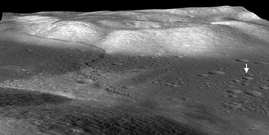 "This undated handout image taken by the NASA's Lunar Reconnaissance Orbiter (LOC) shows the mare basalts that fill the Taurus-Littrow valley were thrust up by contractional forces to form the Lee-Lincoln fault scarp, just west of the Apollo 17 landing site (arrow). The Lunar Reconnaissance Orbiter is revealing previously undetected landforms that indicate the moon is shrinking. The findings are reported in a paper by Smithsonian scientist Thomas Watters, ""Evidence of Recent Thrust Faulting on the Moon Revealed by the Lunar Reconnaissance Orbiter Camera"" scheduled for publication in the Aug. 20 issue of the journal Science. Lobate scarps, imaged by the Lunar Reconnaissance Orbiter Camera, are thrust faults that occur primarily in the lunar highlands. The Photo: Ho, AFP/Getty Images"