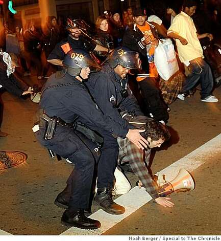 Police tackle a protester during a demonstration in downtown Oakland, Calif. on Wednesday, Jan. 7, 2009. Demonstrators, upset by the fatal shooting by a BART police officer of an unarmed man, smashed a police car, broke car windows and kicked in glass storefronts. Photo: Noah Berger, Special To The Chronicle