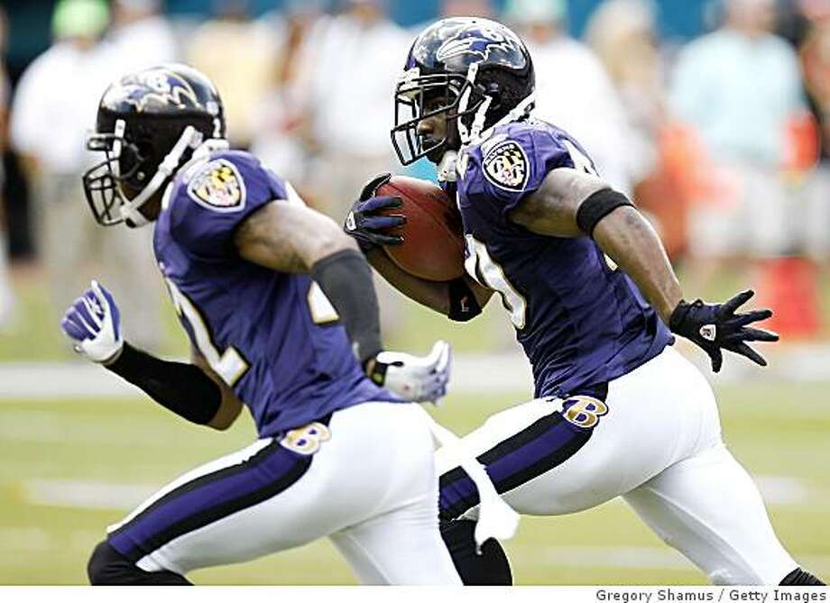 Ravens safety Ed Reed looks for a block by Samari Rolle #22 on his way to a touchdown after a second quarter interception against the Miami Dolphins during an AFC Wild Card playoff game on January 4, 2009 at Dolphin Stadium in Miami. Photo: Gregory Shamus, Getty Images