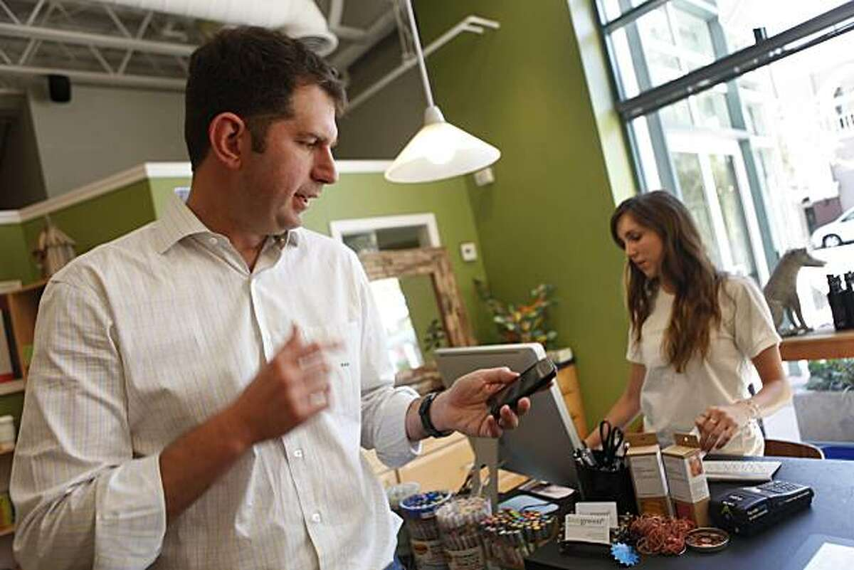 Bling Nation co-CEO Meyer Malek (left) who made his purchase with a Bling tag at Live Greene checks his phone for the receipt after payment in Palo Alto, Calif. on Wednesday August 18, 2010.