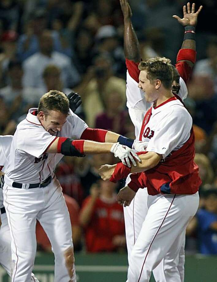 Boston Red Sox's Jed Lowrie, left, celebrates his game-winning home run with Jonathan Papelbon, foreground right, in the eleventh inning of a baseball game against the Toronto Blue Jays in Boston, Saturday, Aug. 21, 2010. The Red Sox won 5-4. Photo: Michael Dwyer, AP