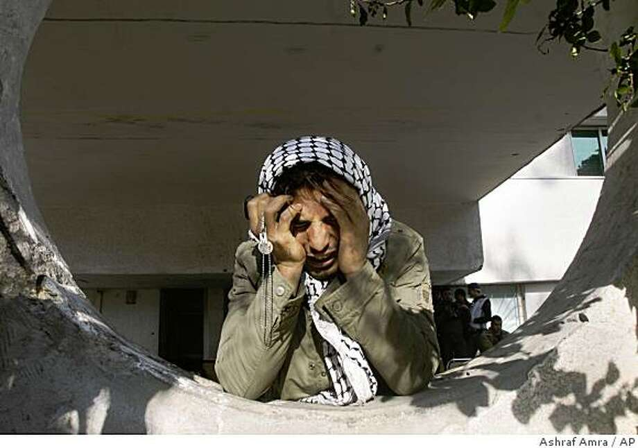 A Palestinian man holds his head in his hands as he reacts at the Shifa Hospital in Gaza City, Monday, Jan. 5, 2009. Israeli forces pounded Gaza Strip houses, mosques and smuggling tunnels on Monday from the air, land and sea, killing at least seven children as they pressed a bruising offensive against Palestinian militants. (AP Photo/Ashraf Amra) Photo: Ashraf Amra, AP