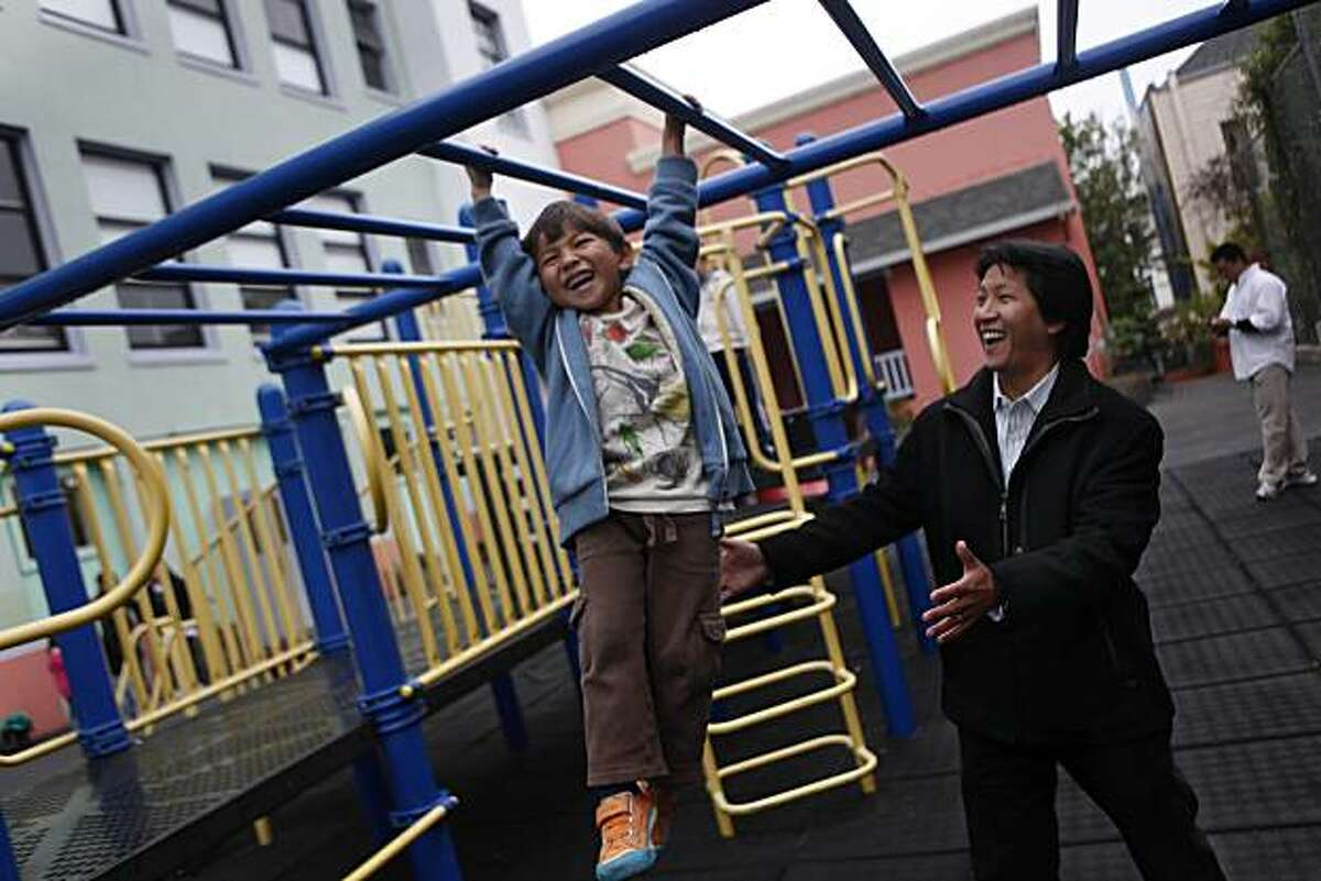 Jack Hsieh (left), 5, swings on the monkey bars at Chinese Immersion School at De Avila as his father, Tom Hsieh (right), Vice President of Fundraising (a PTA position) and is on the School Site Council (an elected position), spots him in San Francisco, Calif. on Friday August 20, 2010.