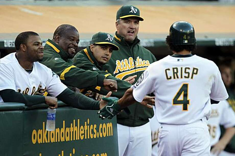 From left, Oakland Athletics' Rajai Davis, trainer Steve Sales, Gio Gonzalez, and manager Bob Geren congratulate Coco Crisp (4) after Crisp scored against the Toronto Blue Jays during the first inning of a baseball game Tuesday, Aug. 17, 2010, in Oakland,Calif. Crisp scored on an RBI double by Daric Barton. Photo: Ben Margot, AP