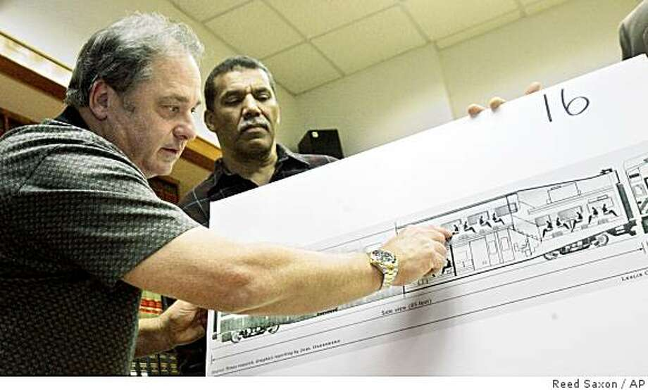 Nicholas Cotsis, left, points to his seat location on a diagram of a typical passenger car as Richard Myles looks on during a news conference at a legal firm representing some of those injured in the September, 2008 collision of a Metrolink communter train and a freight train, in Los Angeles Tuesday, Jan. 6, 2009.  Both were also involved in the 2005 crash of a Metrolink train in Glendale, Calif., and are members of a group that is suing several entities over the September Chatsworth crash that killed 25 and injured hundreds.  (AP Photo/Reed Saxon) Photo: Reed Saxon, AP
