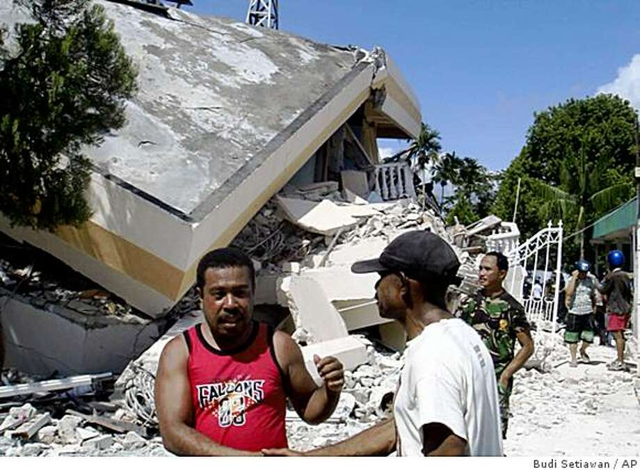 ** RETRANSMISSION UPON REQUEST FROM MULTIPLE SUBS **Residents inspect a collapsed hotel after an earthquake struck in Manokwari, Papua province, Indonesia, Sunday, Jan. 4, 2009. A series of powerful earthquakes at dawn killed at least three people and injured dozens more in remote eastern Indonesia on Sunday, cutting power lines and badly damaging buildings. (AP Photo/Budi Setiawan) Photo: Budi Setiawan, AP