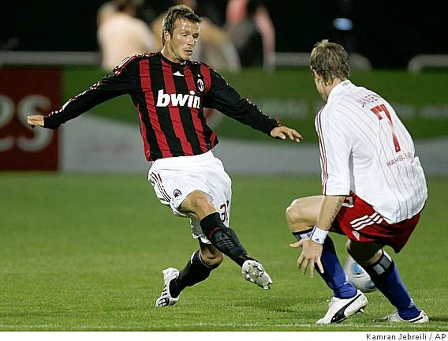 ** CORRECTS YEAR ** AC Milan's David Beckham, left, passes the ball as Marcell Jansen of Hamburg tries to close him down during the friendly soccer match between AC Milan and Hamburg SV in Dubai, United Arab Emirates.Tuesday, Jan. 6, 2009. Beckham is making his first appearance with AC Milan after signing a loan deal from the Los Angeles Galaxy in a bid to prove he can still play at the highest level in Europe. (AP Photo/Kamran Jebreili) Photo: Kamran Jebreili, AP