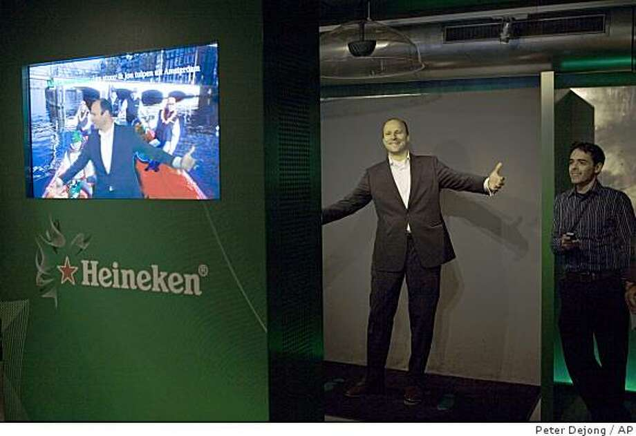 A Heineken official demonstrates a video karaoke attraction at the Heineken Experience, Amsterdam, Netherlands, Tuesday Dec. 9, 2008. The Heineken Experience, a museum where visitors can learn about brewing and the history of Heineken, reopened in December after a major renovation. (AP Photo/Peter Dejong) Photo: Peter Dejong, AP