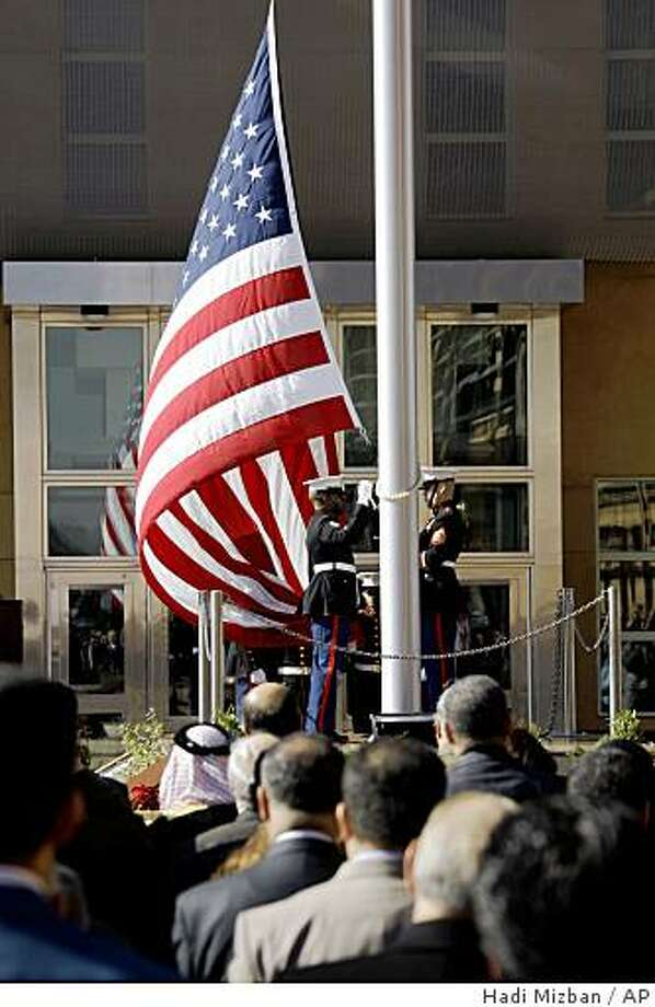 People watch the U.S. flag as it is raised during a ceremony marking the opening of the new U.S. Embassy in Baghdad, Iraq, Monday, Jan. 5, 2009. The embassy in Baghdad is one of the largest U.S. embassies in the world.  (AP Photo/Hadi Mizban) Photo: Hadi Mizban, AP