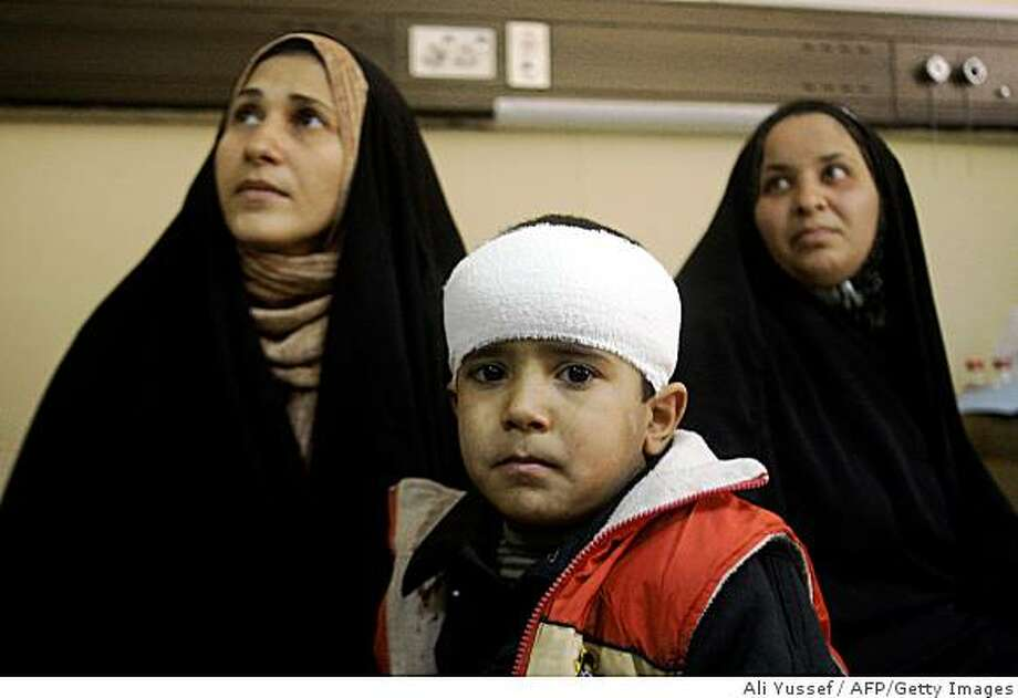 An Iraqi Shiite boy, wounded in a blast near the holy Kadhimiyah shrine, receives treatment at the Kadhimiyah hospital in Baghdad on January 4, 2009. A female suicide bomber killed at least 35 people, including women and children, and wounded 65 others on a religious march near the mausoleum of Imam Mussa al-Kadhim, the most important religious site in Baghdad for Shiite Muslims. AFP PHOTO/ALI YUSSEF (Photo credit should read ALI YUSSEF/AFP/Getty Images) Photo: Ali Yussef, AFP/Getty Images