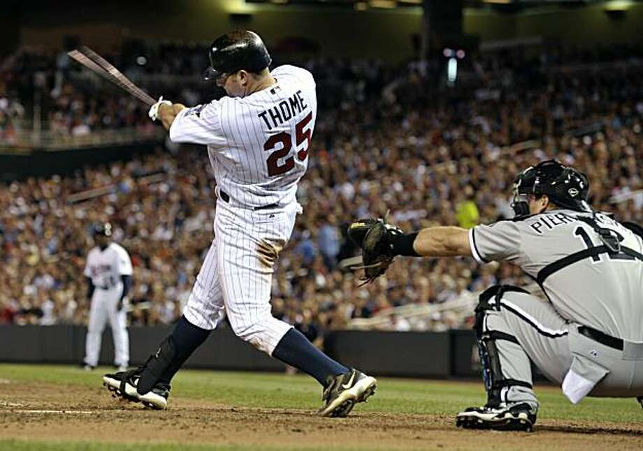 Minnesota Twins' Jim Thome (25) follows through on a two-run home run off Chicago White Sox pitcher Matt Thornton during the 10th inning of a baseball game Tuesday, Aug. 17, 2010, in Minneapolis. White Sox catcher A.J. Pierzynski is at right. The Twins won 7-6. Photo: Tom Olmscheid, AP