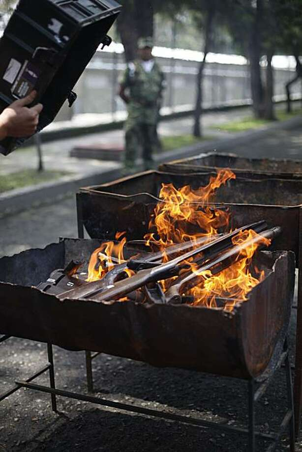 A soldier burns seized weapons from drug smugglers at the Secretary of the Defense headquarters in Mexico City, Wednesday, Aug. 18, 2010. Mexico's drug gang violence has surged since President Felipe Calderon intensified the fight against traffickers in late 2006, deploying thousands of troops and federal police to root out cartels from their strongholds. More than 28,000 people have since been killed in the country's drug war. Photo: Alexandre Meneghini, Associated Press