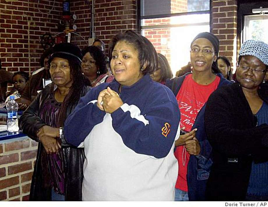 Gloria Nesmith, center, and other parents react at the Ron Clark Academy in Atlanta, Ga., Wednesday, Dec. 31, 2008  to the news that Oprah Winfrey donated $365,000 to the inner-city school. (AP PHOTO/Dorie Turner) Photo: Dorie Turner, AP