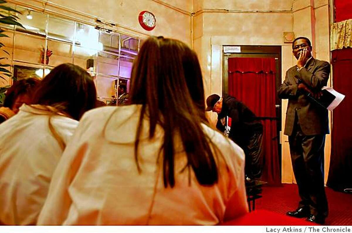 Johnson Ojo (right) questions women as Ed Walsh records their masseuse license on Tuesday Nov. 25, 2008 at the Moonlight Spa on Bush Street in San Francisco, Calif.