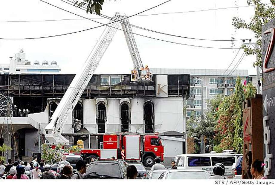 Thai firefighters work at the site of a fire that ripped through a nightclub in Bangkok on January 1, 2009.  Police forensic investigators sifted through the charred remains of an upscale Bangkok nightclub, seeking clues to a blaze that killed 58 revellers ringing in the New Year and injured 223.    AFP PHOTO (Photo credit should read STR/AFP/Getty Images) Photo: STR, AFP/Getty Images