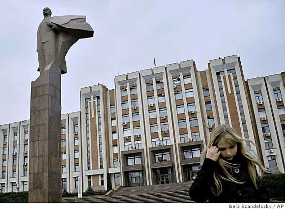 ** ADVANCE FOR TUESDAY, DEC. 30 ** Wind blows the hair of a girl walking by a statue of Lenin in front of the building of the Supreme Council in Tiraspol, Trans-Dniester, a tiny, poor separatist province of Moldova, Thursday, Nov. 6, 2008. Russia is handing out passports to Russian-speaking citizens of a number of states in its sphere of interest, including Trans-Dniester. (AP Photo/Bela Szandelszky) ** NO ONLN ** NO IONLN ** Photo: Bela Szandelszky, AP
