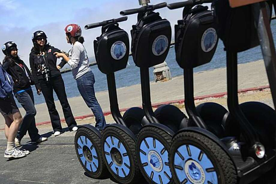 Kristian Ruggieri (right), City Segway Tours tour guide, talks with Christy Clarke (center), of Ashland, Kentucky  and her daughter Milena Clarke (left) during their City Segway Tours tour in San Francisco, Calif. on Tuesday June 22, 2010. Photo: Lea Suzuki, The Chronicle