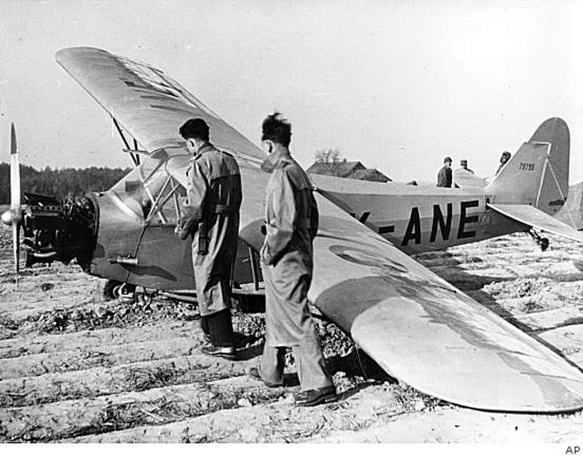 ** FILE ** This file photo from Dec. 1953 shows Jiri Wertheimer, left, and Zdenek Volf inspecting the piper cub airplane in which they made their dramatic escape from communist Czechoslovakia seeking political asylum. The plane landed in a potato field near Pfarrkirchen, Germany in December of 1953 after running out of gas about 30 minutes after crossing the Iron Curtain. (AP Photo/File)