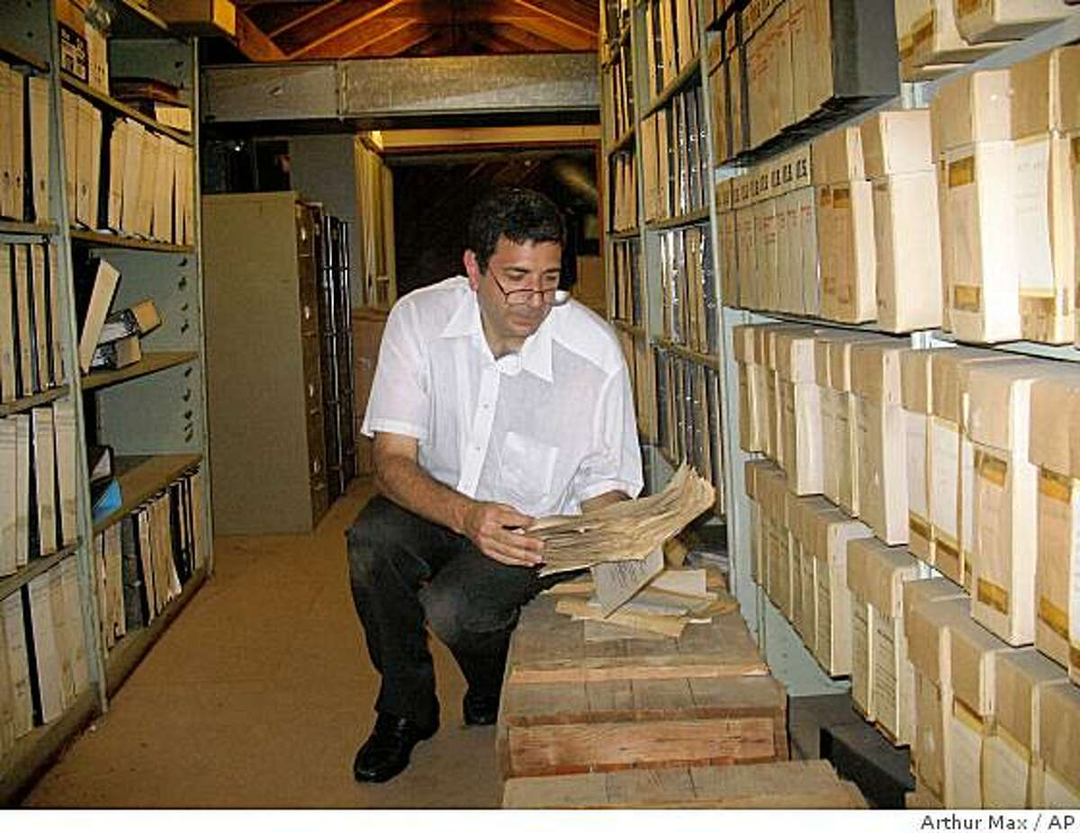 ** CORRECTS NAME OF RESEARCH WORKSHOP PARTICIPATING BODY FROM COMMISSION TO MUSEUM ** ADVANCE FOR MONDAY, DEC. 29 ** AP reporter Randy Herschaft reviews files in the attic of the International Tracing Service in Bad Arolsen, Germany during a research workshop jointly held by the United States Holocaust Memorial Museum and ITS in June 2008. AP reporters who have been allowed repeated access to the archive in the past two years, gained entry to the attic where even employees rarely venture. Cardboard boxes storing old letters were stacked on the floor under the wooden rafters, and binders of inactive and uncatalogued files lined floor-to-ceiling metal shelves. The file on the Escapee Program, apparently undisturbed for many years, harks back to a long forgotten chapter of the Cold War. (AP Photo/Arthur Max) ** NO ONLN ** NO IONLN **